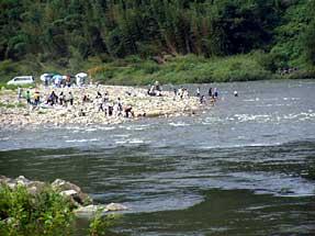 河原でキャンプ、バーベキューを楽しむ人たち